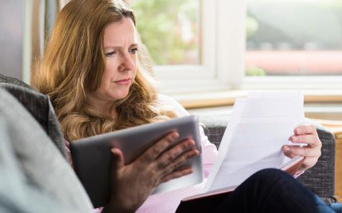 woman-concerned-looking-at-tablet-and-paper-on-couch_573x300